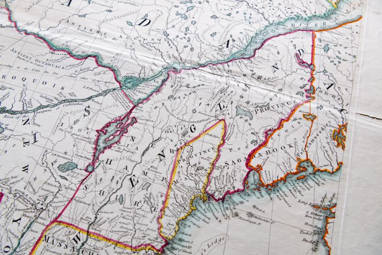 """Detail of a colored, engraved map shows pink, yellow, and green used to outline areas on the mainland and blue to color water. Labels in English over places such as [New] """"England."""""""