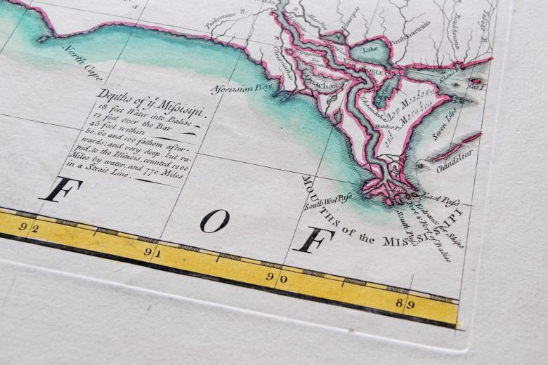"""Detail of a colored, engraved map shows pink used to outline the coastline and blue to color the water. Labels in English over places and text such as """"Depths of ye Missisipi"""" and """"Mouths of the Missisipi."""""""