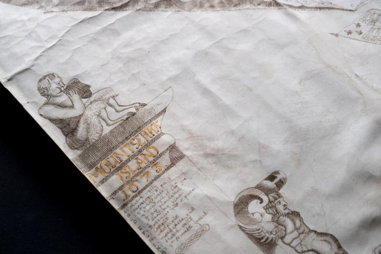 Detail of a manuscript map shows a figure of Pan playing pipes and the title of the map in gold.