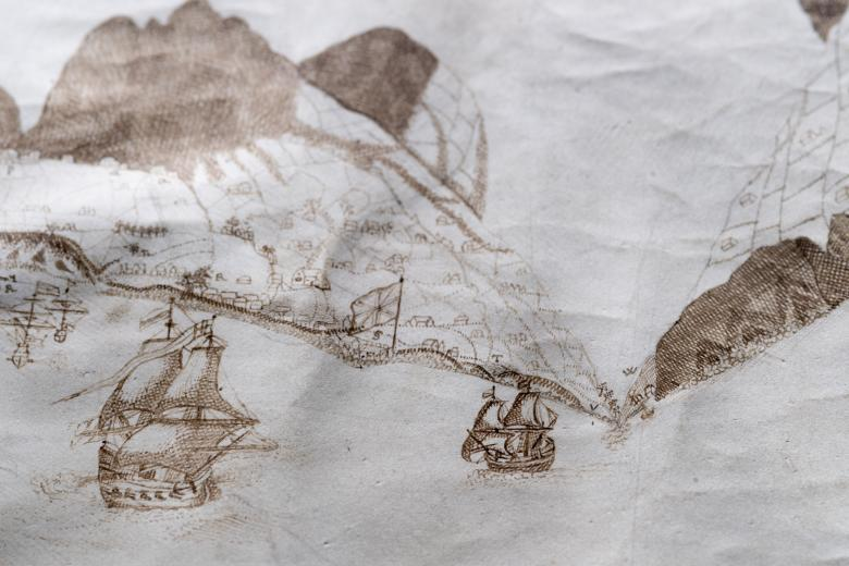 Detail of a manuscript map shows coastal profile and ships at sea. Some buildings are visible within the mountainside.