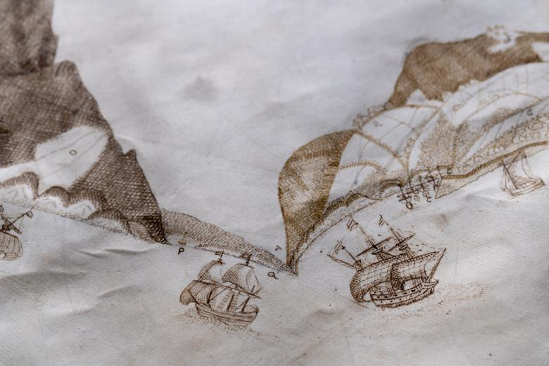 Detail of a manuscript map shows coastal profile and ships at sea. Some letters labeling the mountainside are visible.