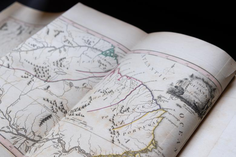 """Detail of an engraved, hand colored map of Guiana with decorative cartouche with map title reading """"A map of Guiana by J. G. Stedman."""" Map includes Portugal, Atlantic Ocean, mountains, and yellow, pink and purple details."""