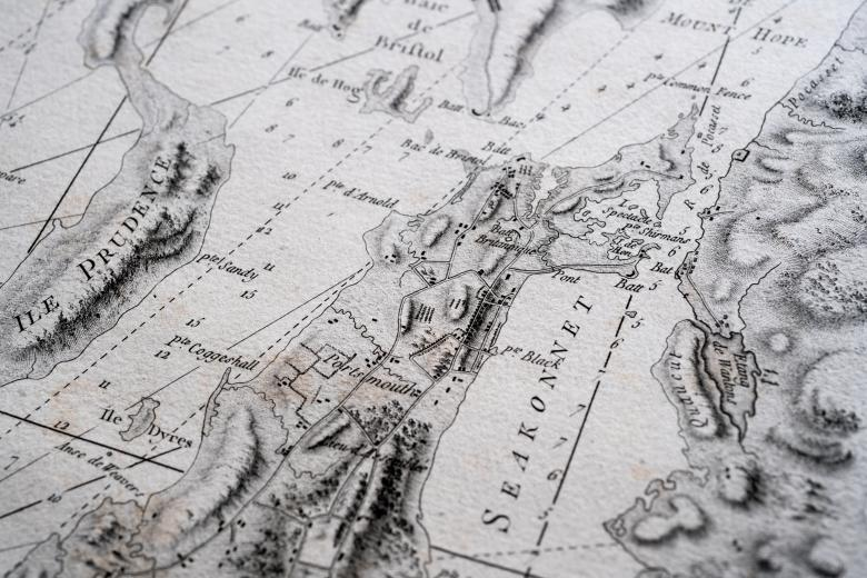 Detail of a printed atlas shows a portion of a map with labels in French, scale, and numbers indicating depth of water.