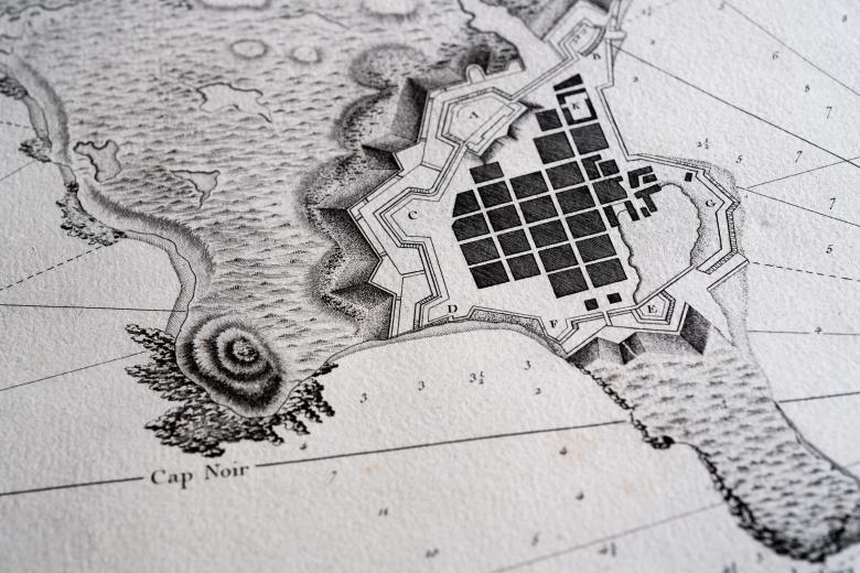 Detail of a printed atlas shows a portion of a map with labels in French and numbers indicating depth of water. Also includes depiction of buildings on land.