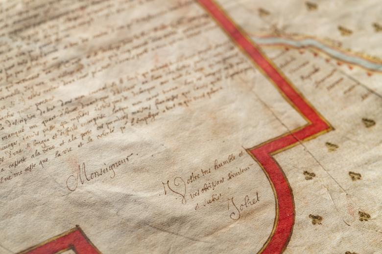 Detail of a manuscript, hand-colored map's cartouche with manuscript text in French and signature of author.
