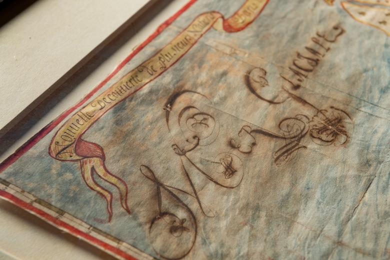Detail of a manuscript, hand-colored map's decorative banner where boththe title and a body of water arehand-writtenin French.