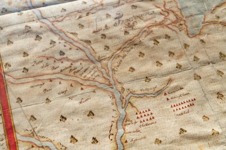 Detail of a manuscript, hand-colored map depicting a river branching off into three directions, scattered trees and red triangles denoting Indigenous villages, and text in French.