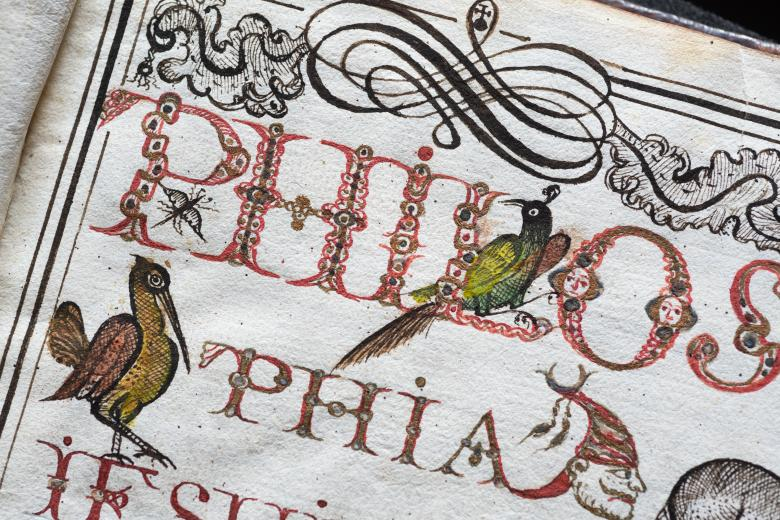 Detail of a manuscript title page shows red and black ink used for titular text and birds.