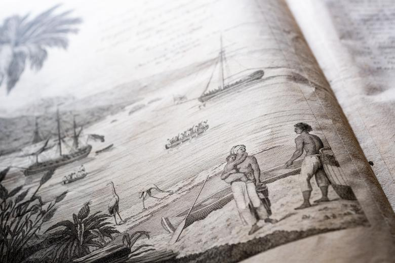 Detail of a printed text shows an illustration where a two men, one of which is carrying a small child, stand on shore talking. Ships at sea are visible in the background.