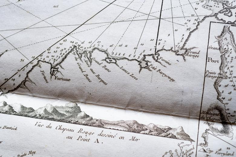 """Detail of a printed map shows latitude and longitude lines and labels in French such as """"Vue du Chapeau Rouge dessiné en Mer au Point A."""""""