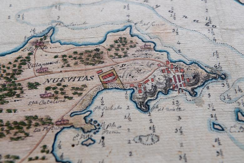 """Detail of a hand-colored manuscript map shows small depth markers, forest, and a label """"Nuevitas"""" and other surrounding landmarks."""