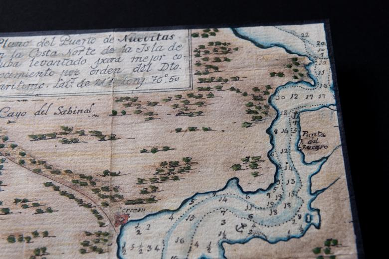 """Detail of a hand-colored manuscript map shows small depth markers, forest, and a label """"Cayo del Sabinal.""""  Manuscript text in Spanish is also visible."""