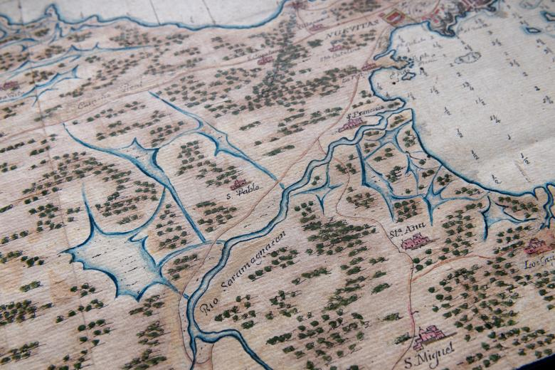 """Detail of a hand-colored manuscript map shows small depth markers, forest, and a labeled river """"Rio Saramaguacan.""""  Other labels in Spanish is also visible."""