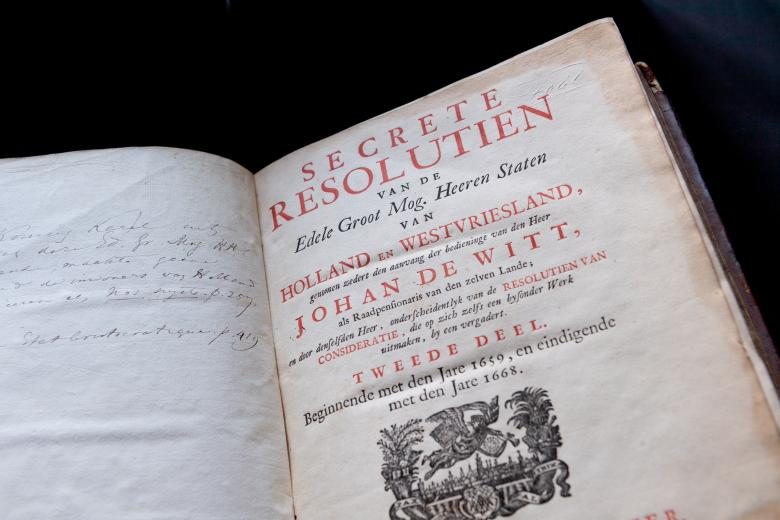 Detail of a printed title page shows red and black used for title text. Decorative sketch of an angel flying low over a city. Manuscript inscription slightly visible on the opposite page.