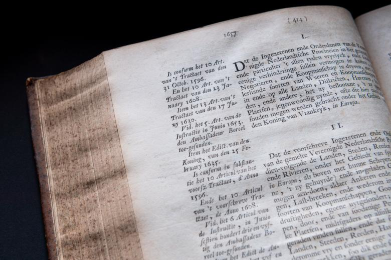 Detail of a printed page shows text main and printed marginalia. Text in Dutch.
