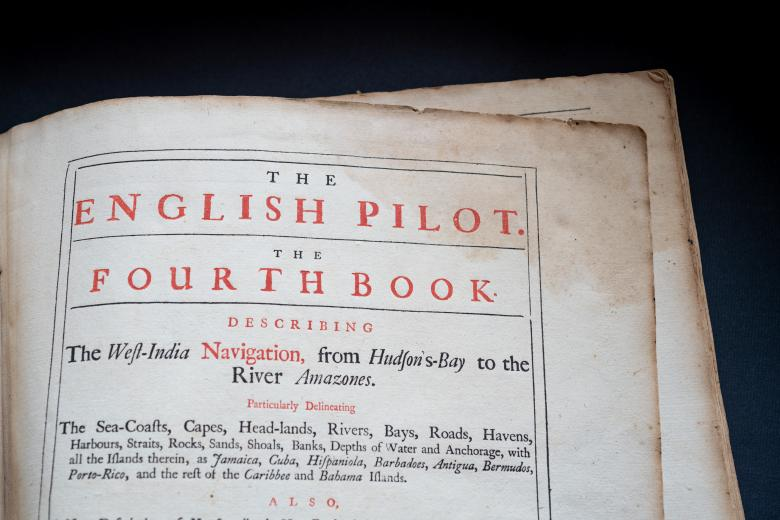 """Detail of a printed book shows title page with English text """"The English Pilot. The Fourth Book describing the West India Navigation, from Hudson's Bay to the River Amazones"""" in red ink."""