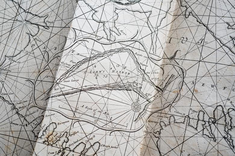"""Detail of a printed map shows a compass rose, latitude and longitude lines, and label for """"St. Johns Harbor"""" and other labels in English."""
