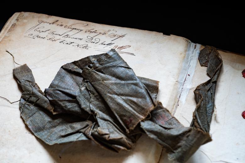 Detail of a book shows manuscript inscriptions and dark grey crumpled paper.