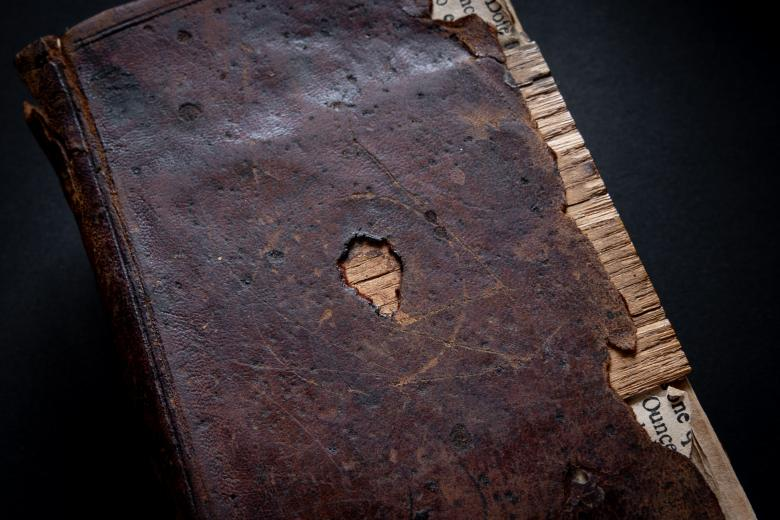 Detail from book cover shows dark brown binding with a missing piece in the front and worn sides.