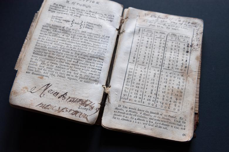 """Detail from printed book opened flat shows text in English on the left side and a chart on the right. Large manuscript writing on the bottom of the left page reads """"Moses Brown."""""""