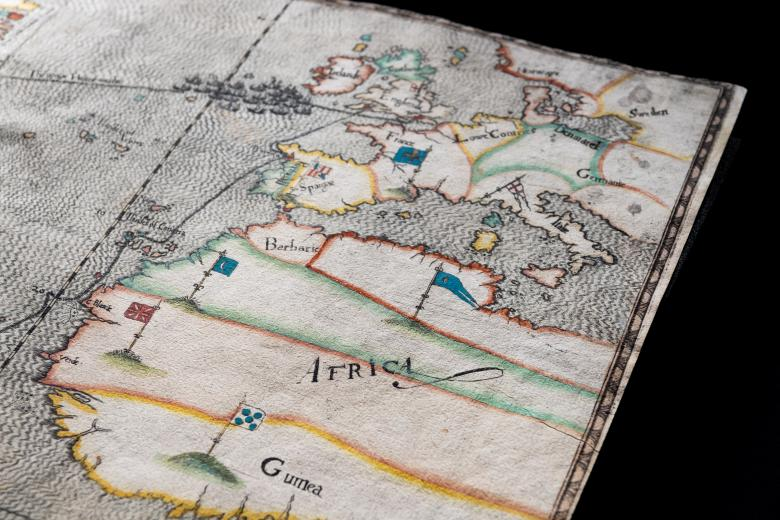 """Detail of a colored, engraved map shows """"Africa"""" and flags."""