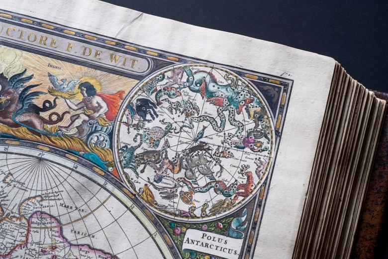 Detail from an engraved, hand colored map shows vivid illustrations of celestial sphere with their constellations and zodiac signs around the sun. Gold-toned title and a chariot pulled by hippocampi or Pegasus are visible.