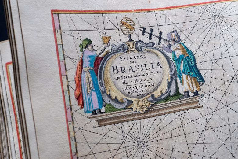 Detail from an engraved, hand colored map shows vivid cartouche that includes text in Dutch, one person hold a cup and another person looks through a telescope.