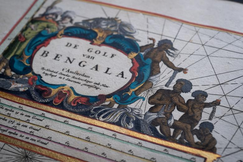 Detail from an engraved, hand colored map shows vivid cartouche includes text in Dutch, black people in white cloths, and the map's scale.