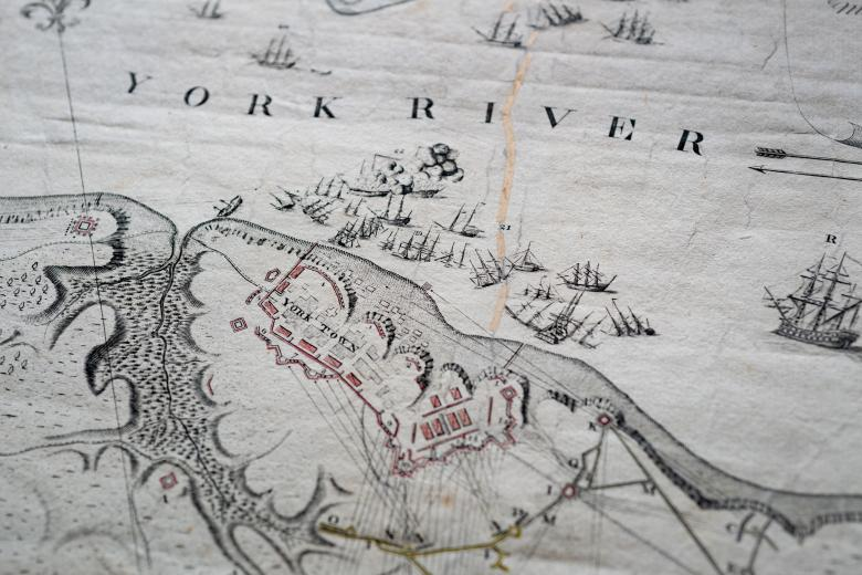 """Detail of an engraved, hand colored map shows naval warfare, labels over """"York River"""" and """"York Town,"""" and red and yellow details."""