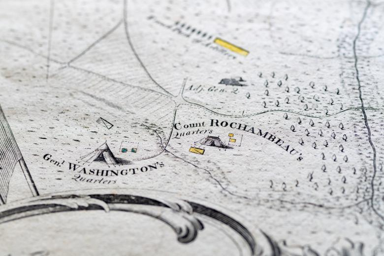 """Detail of an engraved, hand colored map shows a tent labeled """"Gen. Washington's Quarters"""" and """"Count Rochambeau's Quarters"""" with yellow details and forests drawn nearby."""