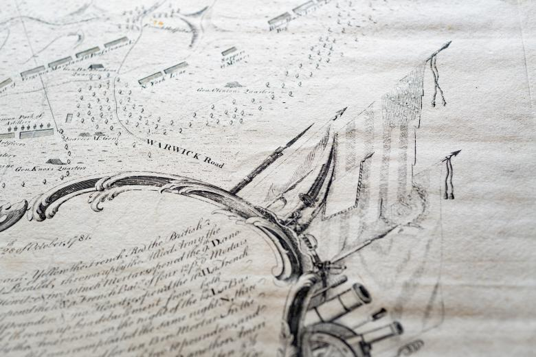 """Detail of an engraved, hand colored map shows labels for """"Warwick Road,"""" flags extending from the cartouche, and a forest nearby."""