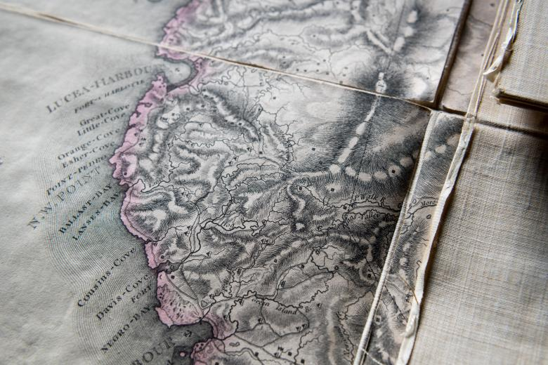 """Detail of an engraved, colored map of Jamaica shows """"Lucea-Harbour,"""" """"Cousins-Cove,"""" among other locations labeled in English. This coastal area is outlined in pink."""