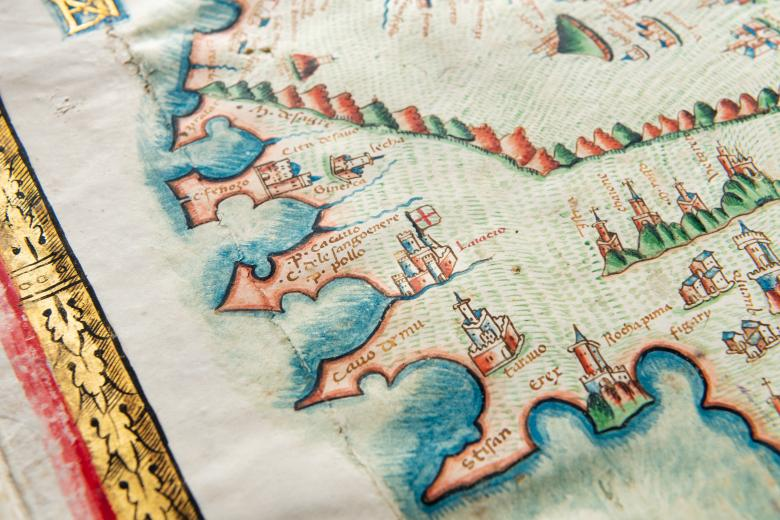 Detail of a colored manuscript atlas shows a coastal region and labels in Latin. Other details include drawings of castles and mountains.