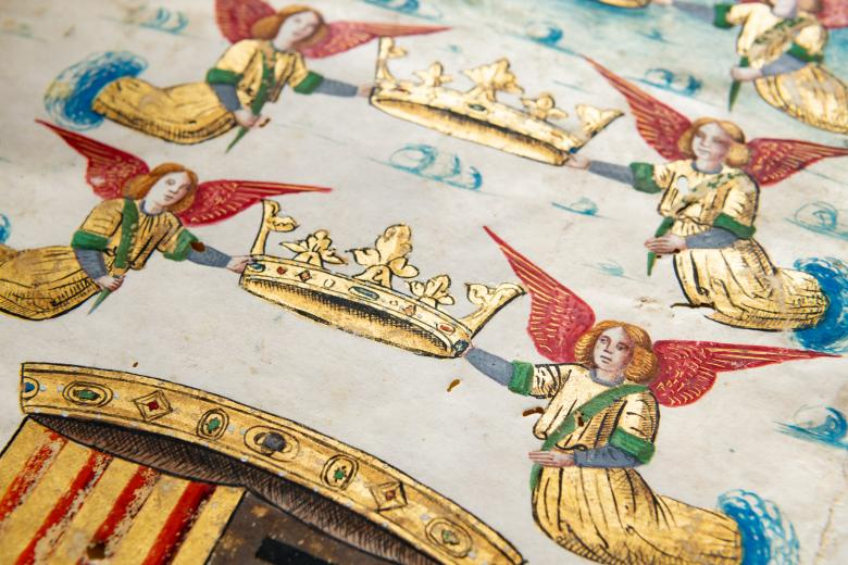 Detail of a colored manuscript atlas shows angels floating among clouds holding crowns.