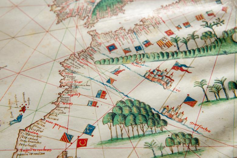 Detail of a colored manuscript atlas shows latitude and longitude lines, forests, and labels in Latin along a coastal region. Other details include castles and flags.