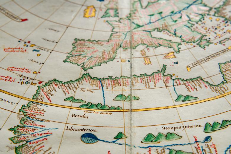Detail of a colored manuscript atlas shows latitude and longitude lines, forests, and labels in Latin along a coastal region. Other details include lakes and gold embellishment.