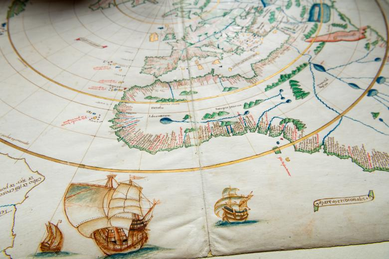 Detail of a colored manuscript atlas shows latitude and longitude lines, forests, and labels in Latin along continents. Other details include ships at sea.