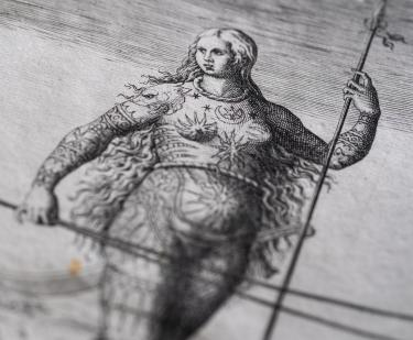 Detail of a printed book shows an illustration of a woman with long hair, elaborate drawings on her body, and holding a spear.