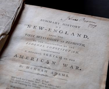 Detail of a printed book shows title page with manuscript notations at the top of the page.