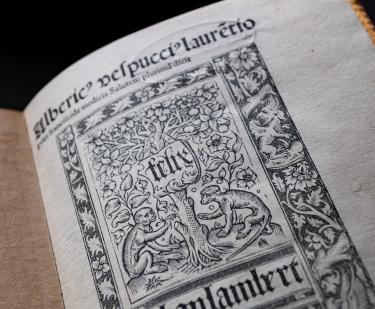 Detail of Mundus Novus' title page which depicts two monkeys sitting by a tree, framed by plants and text in Latin.