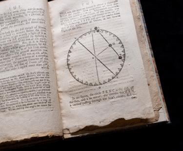 Detail of a printed text shows an astronomical circular diagram and text in English.