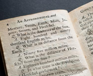 Detail from a printed text shows questions and follow-up answers about astronomy.