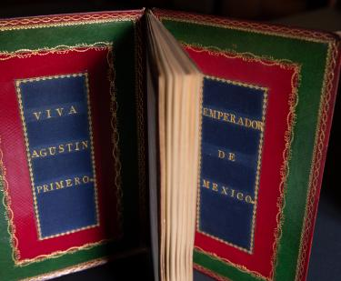 "Printed book bound in red and green Morocco and blue silk with text in Spanish reading ""Viva Agustin Primero"" on the inner front cover and ""emperador de Mexico"" on the inner back cover."