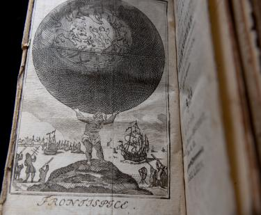 Detail of a printed book shows a full-page illustration on the frontispiece showing a child carrying the world on their shoulders.