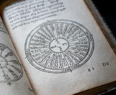 Printed text shows a circular diagram below text in Latin.
