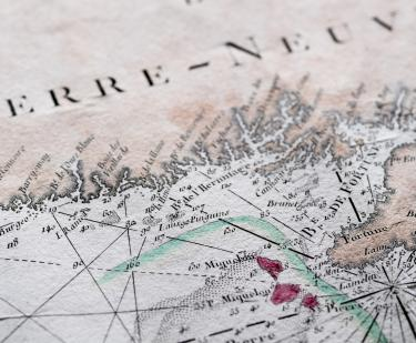 "Detail of a hand colored printed map shows text in French reading ""Terre-Neuve,"" latitude and longitude lines, and labels over other geographical areas."