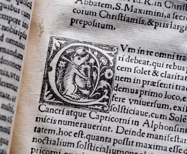 Detail of a printed books shows text in Latin and decorative typography.