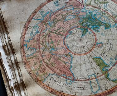 Detail from a colored manuscript map shows the world labeled with text in Latin.