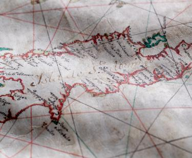 "Detail of a colored manuscript map shows text in Spanish over Hispaniola reading ""Isla de Sto. Domingo"" with other smaller labels."