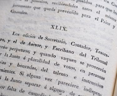 "Detail of a printed book shows text in Spanish reading ""Los oficios de secretario, Contador, tesorero"" and so on."
